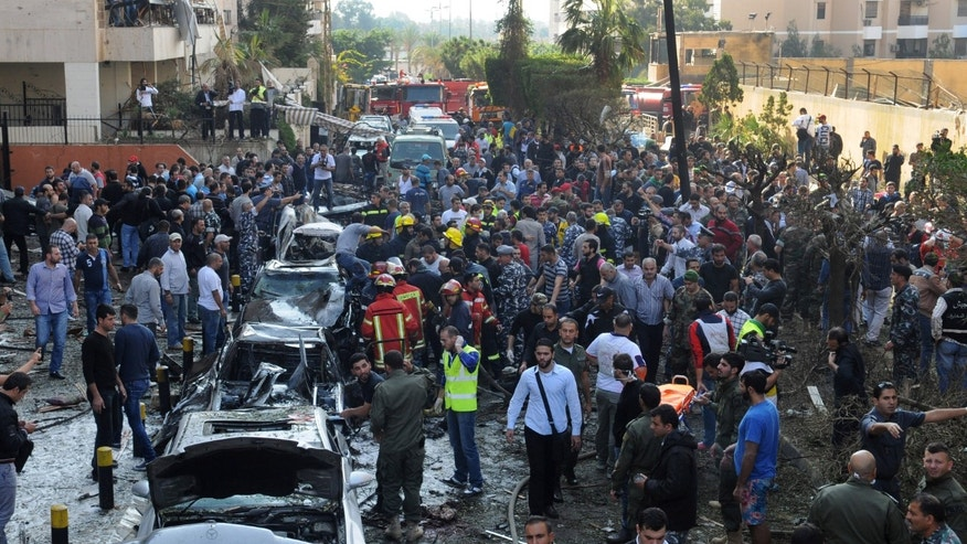 Lebanese citizens and security forces gather near the entrance of the Iranian embassy, background, where two explosions have struck, in Beirut, Lebanon, Tuesday Nov. 19, 2013. Twin suicide bombings struck outside the Iranian Embassy in the Lebanese capital on Tuesday, killing nearly two dozen, including the Iranian cultural attaché, and wounding dozens more in one of the worst bombings to target the predominantly Shiite area in southern Beirut. (AP Photo/Ahmad Omar)