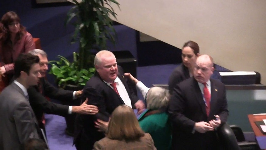 Toronto Mayor Rob Ford is shown in a video frame grab as he knocks down Councillor Pam McConnell as he ran toward hecklers in the audience at City Hall on Monday, Nov. 18, 2013. (AP Photo/The Canadian Press, Paola Loriggio)