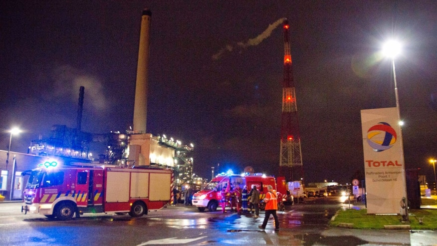 Firemen and rescue personnel stand outside of the Total refinery in the Port of Antwerp, Belgium on Tuesday Nov. 19, 2013. An explosion at Total's Antwerp refinery in Belgium, Europe's second largest port, killed at least one person on Tuesday. (AP Photo/Virginia Mayo)