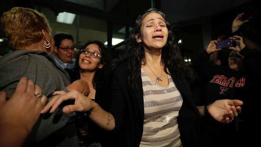 Cassandra Rivera, center, followed by Elizabeth Ramirez and Kristie Mayhugh are greeted by family as they leave the Bexar County Jail, Monday, Nov. 18, 2013, in San Antonio, after it was announced earlier in the day the San Antonio women imprisoned for sexually assaulting two girls in 1994 were expected to walk free Monday after a judge agreed that their convictions were tainted by faulty witness testimony. Vasquez, the fourth, has already been paroled, but under strict conditions. (AP Photo/Eric Gay)