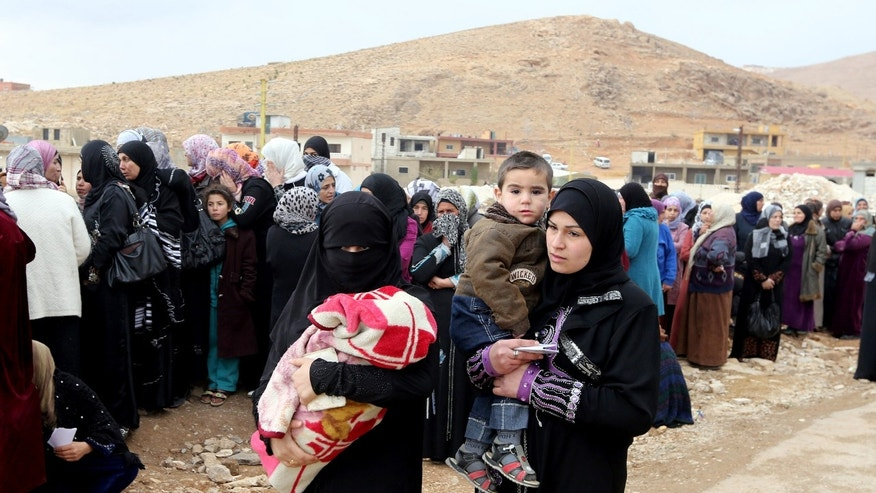 Two Syrian women carry their children as other women stand in line waiting to collect aid from relief agencies helping refugees who fled into the eastern Lebanese border town of Arsal, Lebanon, Monday, Nov. 18, 2013. Thousands of Syrians have fled to Lebanon over the past days as government forces attack the western town of Qarah near the border with Lebanon. (AP Photo/Bilal Hussein)