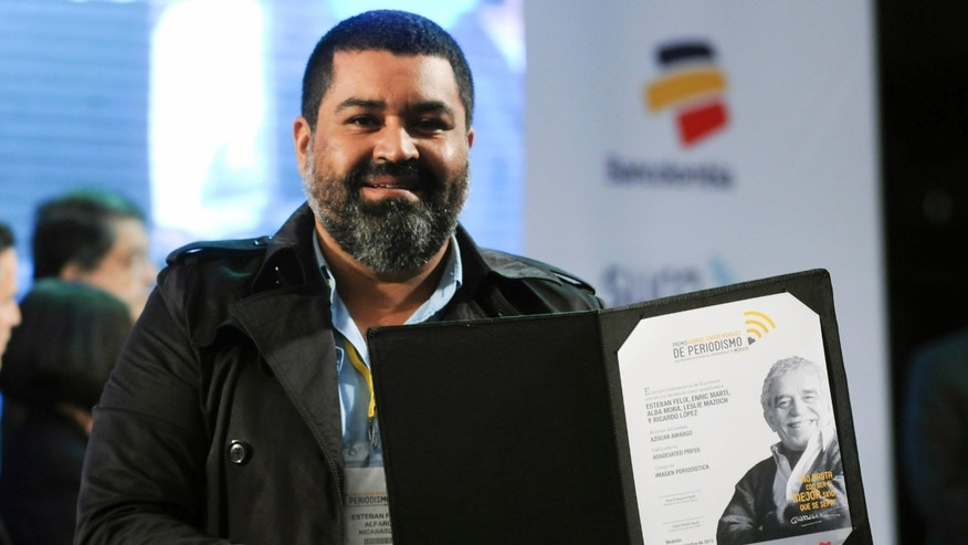 Esteban Felix, an Associated Press photographer from Peru who is based in Nicaragua, shows his Gabriel García Márquez International Journalism Award for visual journalism at the awards ceremony in Medellin, Colombia, Wednesday, Nov. 20, 2013.  Felix was honored for his multimedia project about sugar cane workers affected by chronic kidney disease in Nicaragua. (AP Photo/Luis Benavides)