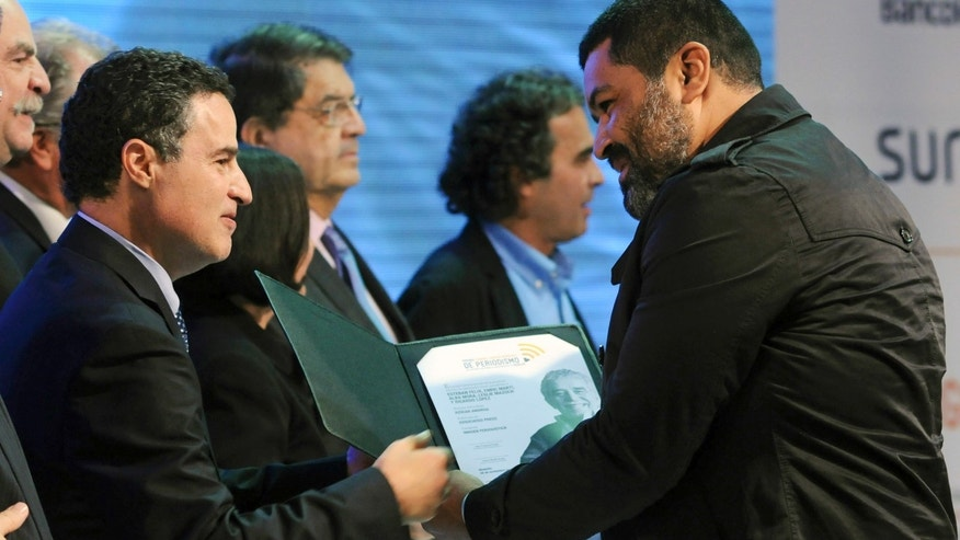Esteban Felix, an Associated Press photographer from Peru who is based in Nicaragua, right, receives the Gabriel García Márquez International Journalism Award for visual journalism from Medellin Mayor Anibal Gaviria at the awards ceremony in Medellin, Colombia, Wednesday, Nov. 20, 2013.  Felix was honored for his multimedia project about sugar cane workers affected by chronic kidney disease in Nicaragua. (AP Photo/Luis Benavides)
