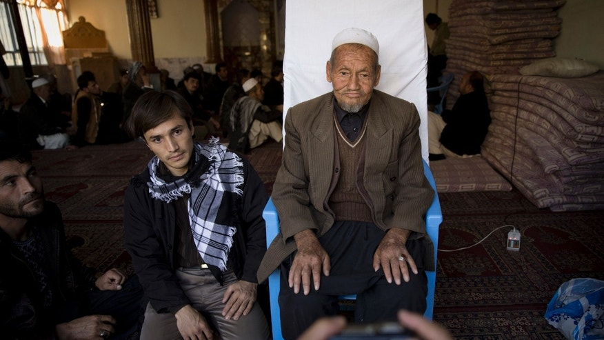 In this Saturday, Nov. 9, 2013 photo, an Afghan man has his picture taken to register for the upcoming Afghan elections in a mosque, used as a mobile voter registration place in Kabul, Afghanistan. The Independent Election Commission (IEC) says a bloated voter registration list is a messy start to the 2014 presidential elections, seen as critical to a stable Afghanistan following the final withdrawal of international combat troops at the end of 2014. (AP Photo/Anja Niedringhaus)