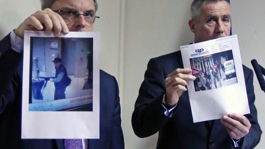 Paris prosecutor Francois Molins, right, and Paris Police executive Christian Flaesch, left, present photos from surveillance cameras showing a gunman leaving BFM television headquarters, left, and in a Paris street near Liberation newspaper, right, during a press conference in Paris, Monday Nov. 18, 2013. Francois Molins says a lone gunman appears to be behind a shooting at a Paris newspaper office that gravely wounded a photographer, and three other attacks. He said the gunman opened fire at the prominent daily Liberation on Monday morning. Soon afterward, shots were fired at the headquarters of French bank Societe Generale west of Paris.(AP Photo/Remy de la Mauviniere)