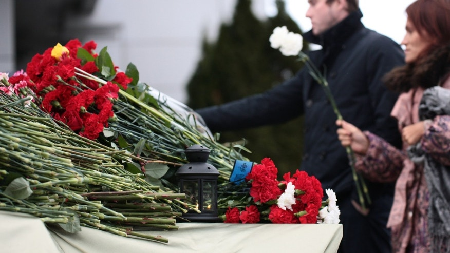 People place flowers in Kazan airport Monday, Nov. 18, 2013. A plane belonging to Tatarstan Airlines crashed Sunday while trying to land at its home port in the Russian city of Kazan, the capital of the oil-rich province of Tatarstan. The son of the provincial governor and the chief of the local branch of Russia's main security agency were among the victims. (AP Photo/ Nikolai Alexandrov)