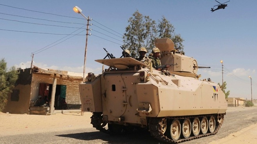 May 21, 2013: In this file photo, Egyptian Army soldiers patrol in an armored vehicle backed by a helicopter gunship during a sweep through villages in Sheikh Zuweyid, northern Sinai, Egypt.
