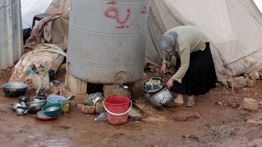 A Syrian refugee woman washes dishes outside her tent in a refugee camp in the eastern Lebanese border town of Arsal, Lebanon, Monday, Nov. 18, 2013. Thousands of Syrians have fled to Lebanon over the past days as government forces attack the western town of Qarah near the border with Lebanon. (AP Photo/Bilal Hussein)