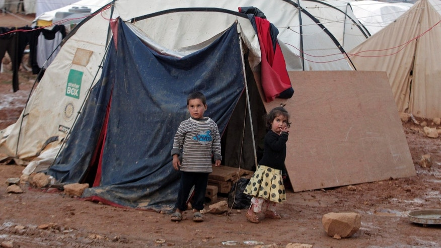 CAPTION CORRECTION, CORRECTS SPELLING OF TOWN - Syrian children stand near their tent at a refugee camp in the eastern Lebanese border town of Arsal, Lebanon, Monday, Nov. 18, 2013. Thousands of Syrians have fled to Lebanon over the past days as government forces attack the western town of Qara near the border with Lebanon. (AP Photo/Bilal Hussein)
