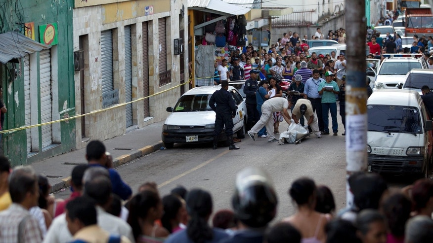 "In this Nov. 19, 2013 photo, people watch forensic workers carry away the body of taxi driver Benjamin Alvarez Moncada in downtown Tegucigalpa, Honduras. The 68-year-old taxi driver known as ""Don Mincho"" expected a passenger to emerge from the throngs headed home after work as usual on Tuesday afternoon. Instead, a 15-year-old sidled up to his taxi with a revolver and fired three shots, hitting him in the chest, ear and neck in what was seen as an attack on a group of taxi drivers whose members didn't make a recent payment to a criminal gang because they couldn't afford it and complained to police. (AP Photo/Moises Castillo)"