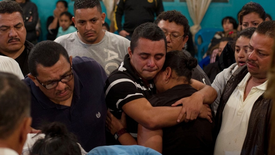 "Relatives cry over the coffin of Benjamin Alvarez Moncada or ""Don Mincho,"" as the 68-year-old taxi driver was called, at the New Dawn church in El Bosque neighborhood in Tegucigalpa, Honduras, early Wednesday morning, Nov. 20, 2013. Fellow taxi drivers say Don Mincho was killed in an apparent attack on the entire taxi collective for recently not making its regular extortion payment to a criminal gang because members didn't have enough money and for making a police complaint. (AP Photo/Moises Castillo)"