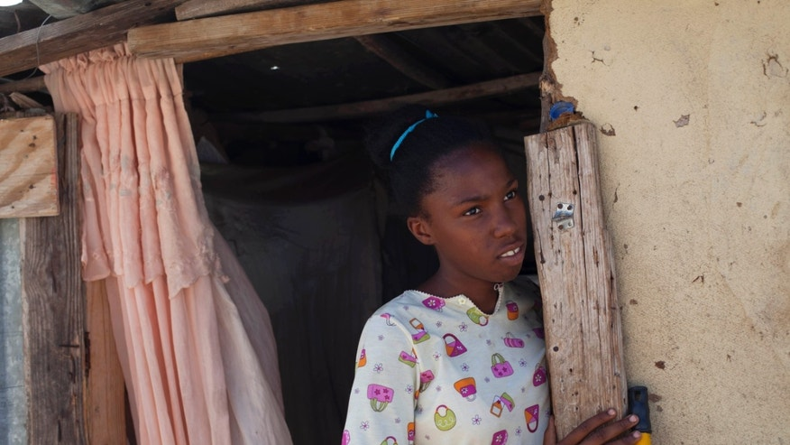 In this photo Nov. 12, 2013 photo, Nelie Charles, 13, one of many people of Haitian descent fearing the effects of a recent Dominican court ruling on citizenship, stands in the doorway of her home in Jimani, Dominican Republic, near the border with Haiti. There are accounts of people who have been reported to immigration authorities and deported after squabbling with their neighbors or being abruptly thrown out of the country at a time when their employers are having financial difficulties. (AP Photo/Dieu Nalio Chery)