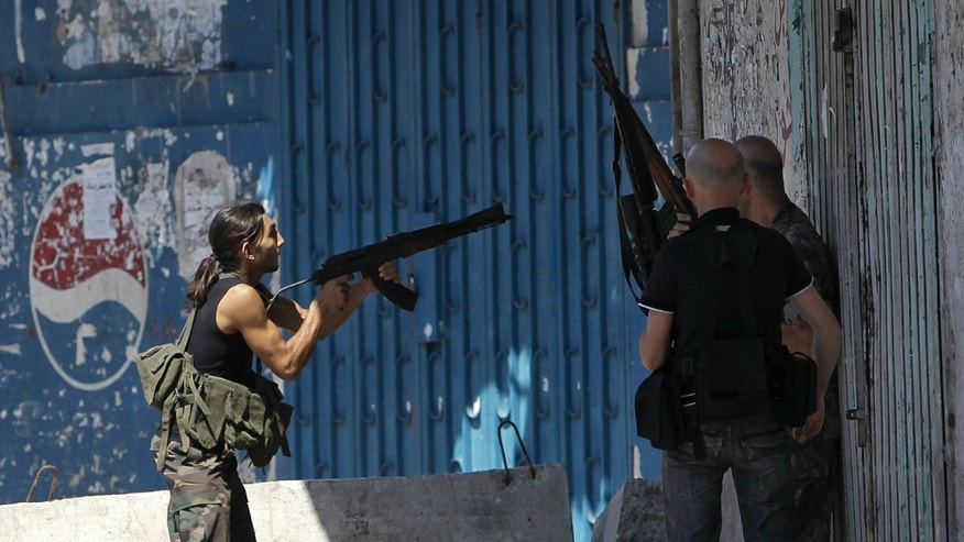 FILE - In this Friday, Aug. 24, 2012 file photo, a Sunni gunman, left, fires his AK-47 machine gun during clashes that erupted between pro and anti-Syrian regime gunmen in the northern port city of Tripoli, Lebanon. The conflict has rippled across the Middle East, sending more than 2 million refugees spilling across Syria's borders, stoking Sunni-Shiite tensions to levels unseen in years and rattling the very foundations of the region's nation states. The most fragile of those is Lebanon, which is still recovering from its own bloody 15-year civil war and has long been seen as no more than a nudge away from tumbling back into full-blown confessional conflict. (AP Photo/Hussein Malla, File)
