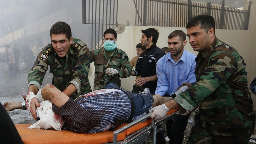 FILE - In this Tuesday, Nov. 19, 2013 file photo, Lebanese army soldiers help an injured man at the scene where two explosions have struck near the Iranian Embassy killing several, in Beirut, Lebanon. The conflict has rippled across the Middle East, sending more than 2 million refugees spilling across Syria's borders, stoking Sunni-Shiite tensions to levels unseen in years and rattling the very foundations of the region's nation states. The most fragile of those is Lebanon, which is still recovering from its own bloody 15-year civil war and has long been seen as no more than a nudge away from tumbling back into full-blown confessional conflict. (AP Photo/Hussein Malla, File)