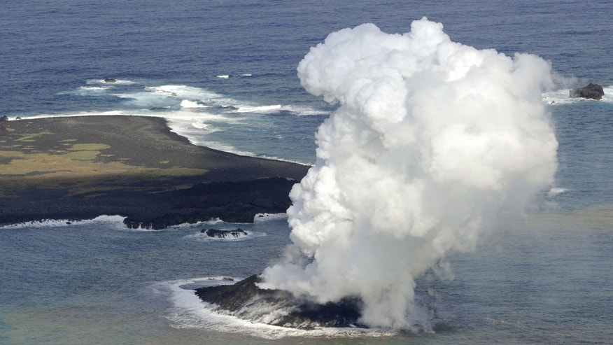 Smoke billows from a new island off the coast of Nishinoshima, seen left above, a small, uninhabited island in the Ogasawara chain, far south of Tokyo Thursday, Nov. 21, 2013. The Japan Coast Guard and earthquake experts said a volcanic eruption has raised the new island in the seas to the far south of Tokyo. The coast guard issued an advisory Wednesday warning of heavy black smoke from the eruption. (AP Photo/Kyodo News) JAPAN OUT, MANDATORY CREDIT