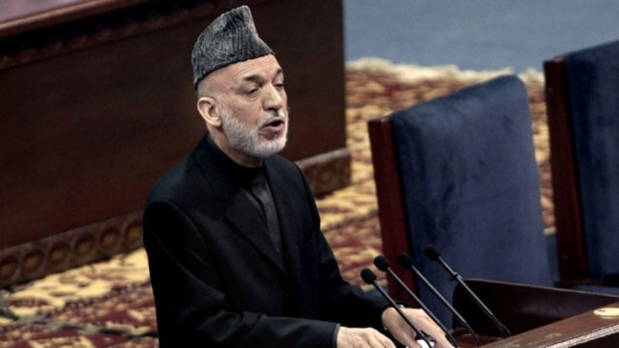 November 21, 2013: Afghan President Hamid Karzai speaks during the first day of the Loya Jirga in Kabul, Afghanistan. Karzai has told a gathering of elders that he supports signing a security deal with the United States if safety and security conditions are met. (AP Photo)