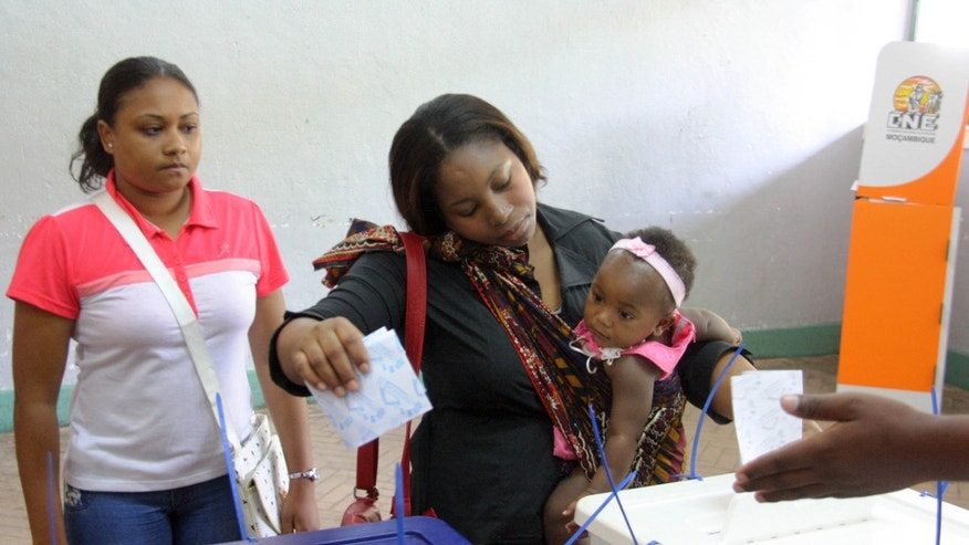 A woman holding her baby casts her vote, during municipal elections held in the city of Maputo, Mozambique, Wednesday,  Nov. 20, 2013. Mozambicans are voting in municipals elections amid tension and sporadic violence between the government and the main opposition group, which says it is boycotting the election. State radio said voting was proceeding peacefully on Wednesday, a day after the opposition Renamo group said it had no intention of disrupting the vote.  (AP Photo/Ferhat Momade)