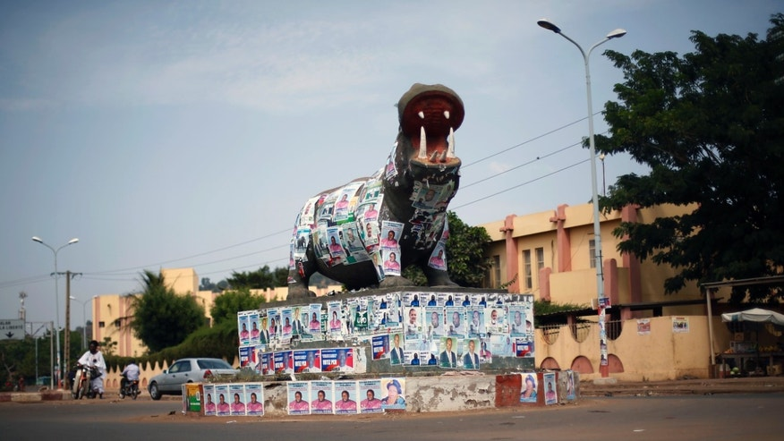 A statue of a hippopotamus is covered with election posters at a traffic circle in Bamako, Mali, Tuesday Nov. 19, 2013. Mali is scheduled to hold parliamentary elections on Sunday, Nov. 24, 2013, in an effort to finalize a return to democracy after a 2012 military coup. Last week residents reported an increase in armed Tuareg rebels in the northern Mali town of Kidal, underscoring the security risks that remain even after a French-led military intervention ousted al-Qaida-linked militants from the major towns in the region. (AP Photo/Jerome Delay)