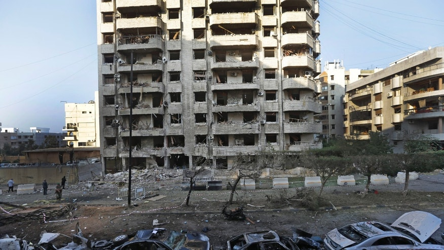 Damaged cars are seen in front of a building where many Iranian diplomats live, at the scene of two explosions, that struck the day before, near the Iranian embassy, in Beirut, Lebanon, Wednesday, Nov. 20, 2013. Twin suicide bombings struck outside the Iranian Embassy in the Lebanese capital on Tuesday, killing nearly two dozen, including the Iranian cultural attaché, and wounding dozens more in one of the worst bombings to target the predominantly Shiite area in southern Beirut. The double bombing pulled Lebanon further into the neighboring Syrian conflict that has torn apart the deeply divided country. (AP Photo/Hussein Malla)