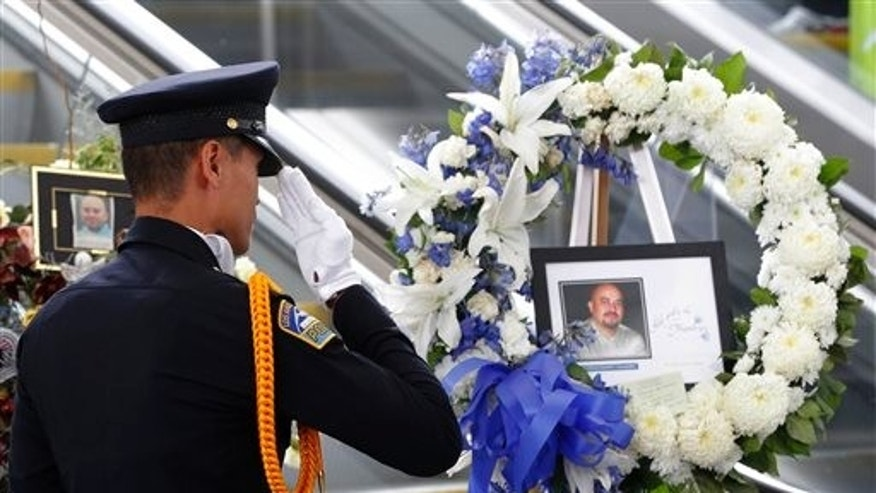 TSA officer Fritz Corros salutes at Los Angeles International Airport, during a moment of silence Friday Nov. 8, 2013, to honor the Transportation Security Administration officer Gerardo Hernandez, killed by a gunman at the airport a week ago.(AP Photo/Nick Ut)