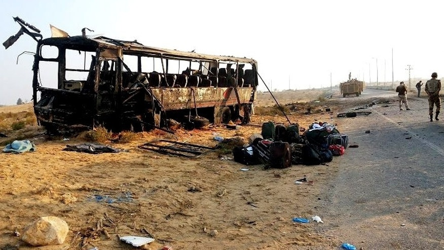 FILE - In this Wednesday, Nov. 20, 2013 file image released on the official Facebook page of the Egyptian Military Spokesman of the Armed Forces, Egyptian military soldiers inspect the scene near a destroyed bus, after a suicide attacker hit his explosive-laden car into the bus at the road between the border town of Rafah and the coastal city of el-Arish, Egypt. In Egypt, misery just keeps piling and, fittingly, the nation is officially in mourning. Political violence and unrest have plagued Egypt since the ouster in 2011 of longtime authoritarian ruler Hosni Mubarak, but a flurry of deadly incidents this week appears to have touched a raw nerve in the nation's psyche, with many Egyptians abandoning hopes for democracy and freedom and instead embracing a grim view of the future. (AP Photo/The Official Facebook Page of the Egyptian Military Spokesman of the Armed Forces, File)