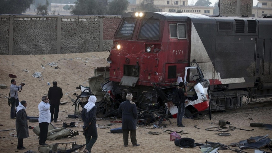 FILE - In this file photo taken Monday, Nov. 18, 2013, journalists and others inspect the wreckage of vehicles struck by a train at the site of a deadly train accident near the village of Dahshur, about 40 kilometers (25 miles) south of Cairo, Egypt. In Egypt, misery just keeps piling and, fittingly, the nation is officially in mourning. Political violence and unrest have plagued Egypt since the ouster in 2011 of longtime authoritarian ruler Hosni Mubarak, but a flurry of deadly incidents this week appears to have touched a raw nerve in the nation's psyche, with many Egyptians abandoning hopes for democracy and freedom and instead embracing a grim view of the future. (AP Photo/Ahmed Gomaa, File)