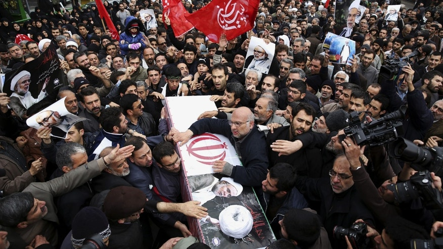"""Iranians carry the coffin of Ibrahim Ansari, Iran's cultural adviser killed Tuesday in Lebanon, after Friday prayer in Tehran, Iran, Friday, Nov. 22, 2013. Ansari was a victim of a twin suicide bombing outside the Iranian Embassy in Beirut Tuesday. The Arabic on the red flag reads, """"Yes to Hussein,"""" from Islamic religious verse. (AP Photo/Ebrahim Noroozi)"""