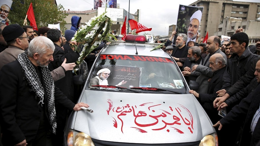 """Iranians send off an ambulance car carrying the coffin of Ibrahim Ansari, Iran's cultural adviser killed Tuesday in Lebanon, after Friday prayer in Tehran, Iran, Friday, Nov. 22, 2013. Ansari was a victim of a twin suicide bombing outside the Iranian Embassy in Beirut Tuesday. The Arabic on the vehicle reads, """"Oh the moon of Hashim's family,"""" also known as Abbas, Imam Hussein's brother from Islamic religious verse. (AP Photo/Ebrahim Noroozi)"""