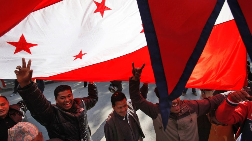 Supporters of the Nepali Congress party hold their party flag as their candidates are displayed on a screen outside a vote counting center in Katmandu, Nepal, Thursday, Nov. 21, 2013. The leader of Nepal's Maoist party, who appears to have lost in this week's national election, demanded Thursday that the vote counting be stopped because of what he called massive irregularities. (AP Photo/Niranjan Shrestha)