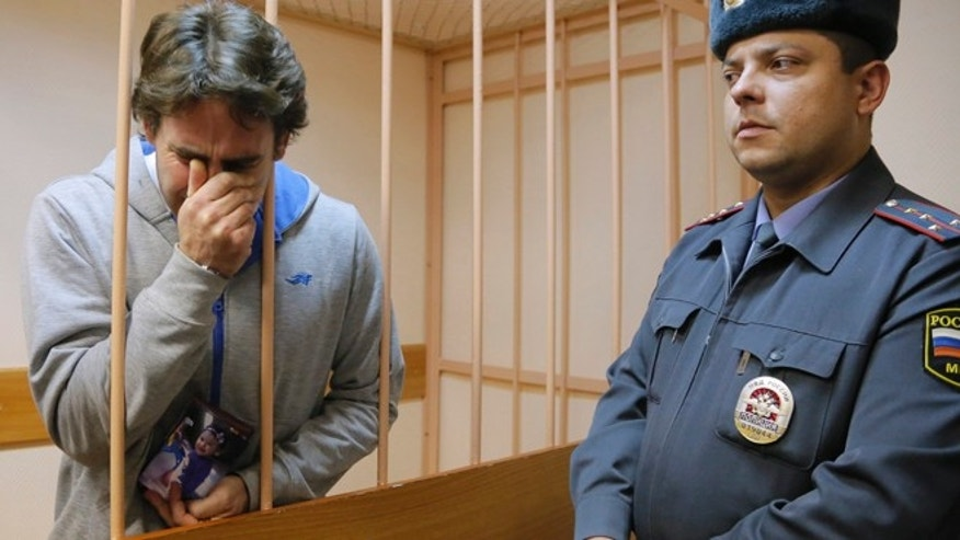 Nov. 19: Greenpeace International activist Miguel Hernan Perez Orsi of Argentina, left, reacts to a verdict and holds a photo of his daughter in a cage at a court room during a hearing.