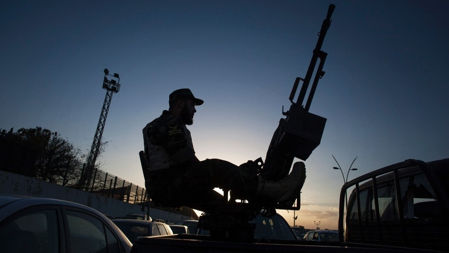 A Libyan army soldier stands guard sitting on an antiaircraft truck during the handover of the Nawaseen military compound, which was the headquarters of Libyan militias, in Souk al-Juma district, Tripoli, Libya, Thursday, Nov. 21, 2013. Militias from a string of Libyan cities left the capital, Tripoli, on Thursday, nearly a week after militiamen killed more than 40 people protesting their presence in the city. The withdrawal is a triumph for the residents of Tripoli, who on Nov. 15 held a mass protest against the militias, which have fueled lawlessness nationwide since the 2011 fall of longtime dictator Moammar Gadhafi. (AP Photo/Manu Brabo)