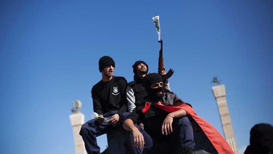 In this photo taken Thursday, Nov. 21, 2013, a member of the Libyan police special forces holds his weapon with a flower inserted in its barrel while he and others sit atop a vehicle at Martyrs' Square, also known as Green Square, in Tripoli, Libya. Militias from a string of Libyan cities left Tripoli on Thursday. The withdrawal is a triumph for the residents of Tripoli, who on Nov. 15 held a mass protest against the militias, which have fueled lawlessness nationwide since the 2011 fall of longtime dictator Moammar Gadhafi. (AP Photo/Manu Brabo)