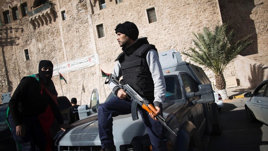 In this photo taken Thursday, Nov. 21, 2013, a member of the Libyan police special forces holds his weapon as he and another stand atop a vehicle at Martyrs' Square, also known as Green Square, in Tripoli, Libya. Militias from a string of Libyan cities left Tripoli on Thursday. The withdrawal is a triumph for the residents of Tripoli, who on Nov. 15 held a mass protest against the militias, which have fueled lawlessness nationwide since the 2011 fall of longtime dictator Moammar Gadhafi. (AP Photo/Manu Brabo)