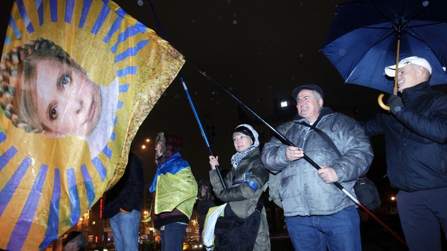 Activists hold a flag with the image of former Ukrainian Prime Minister Yulia Tymoshenko during a night rally in support of Ukraine's integration with the European Union in the center of Kiev, Ukraine, Friday, Nov. 22, 2013. Ukraine's president-controlled parliament on Thursday failed to pass any of a flurry of proposed bills allowing the release of jailed former premier Yulia Tymoshneko, dealing a harsh blow to this ex-Soviet republic's chances of integration with the European Union. (AP Photo/Sergei Chuzavkov)