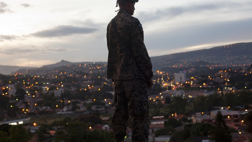 A soldier stands guard outside the National Party headquarters where presidential candidate Juan Orlando Hernandez gives a press conference in Tegucigalpa, Honduras, Thursday, Nov. 21, 2013. Honduras will hold general elections on Nov. 24. (AP Photo/Moises Castillo)