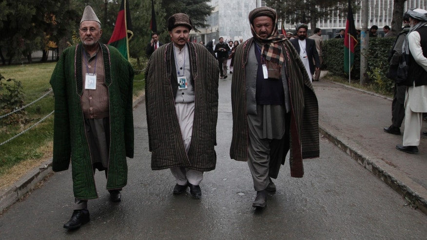 Afghan delegates walk on the street on the third day of the Loya Jirga, or the consultative council in Kabul, Afghanistan, Saturday, Nov. 23, 2013. Representatives from different groups gather in separate rooms and discuss until meeting again in the council. President Hamid Karzai on Friday rebuffed American demands that he sign a security pact allowing U.S. forces to stay in the country for another decade, while the U.S. defense secretary warned that planning for a post-2014 military presence may be jeopardized if the deal isn't finalized by the end of the year. (AP Photo/Rahmat Gul)