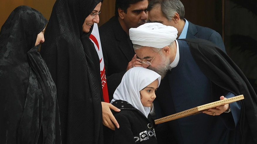 In this photo released by the official website of the office of the Iranian Presidency, Iran's President Hassan Rouhani kisses the head of Armita, daughter of Iranian scientific researcher Darioush Rezaeinejad who was assassinated in July 2011, during a news briefing after Iran and world powers came to an agreement in Geneva over its nuclear program, at the Presidency compound in Tehran, Iran, Sunday, Nov. 24, 2013. Iran struck a historic deal Sunday with the United States and five other world powers, agreeing to a temporary freeze of its nuclear program in the most significant agreement between Washington and Tehran in more than three decades of estrangement. (AP Photo/Presidency Office, Mohammad Berno)