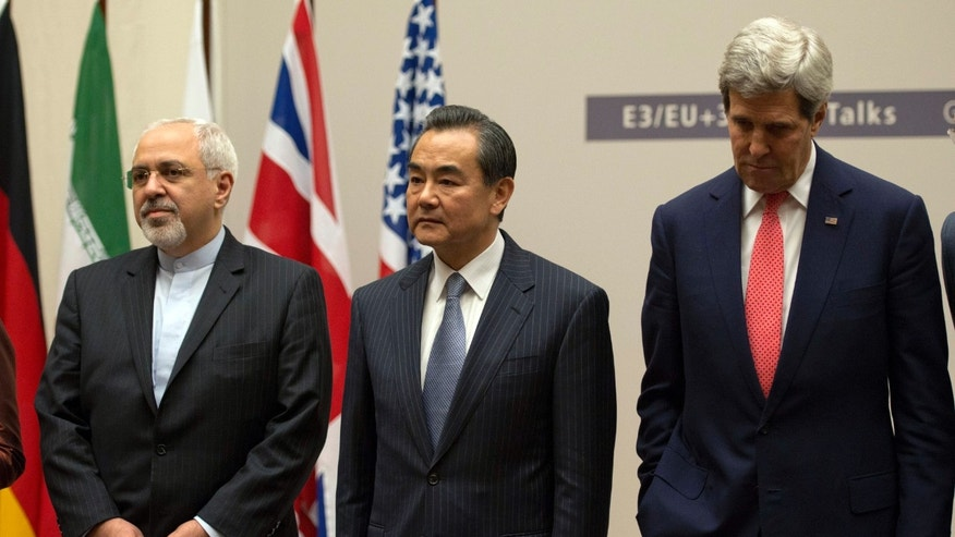 Iranian Foreign Minister Mohammad Javad Zarif, left, Chinese Foreign Minister Wang Yi, center, and U.S. Secretary of State John Kerry, right, attend a ceremony after an agreement was reached on Iran's nuclear program at the United Nations in Geneva, Switzerland, Sunday, Nov. 24, 2013. Iran struck a historic nuclear deal Sunday with the United States and five other world powers, in the most significant development between Washington and Tehran in more than three decades of estrangement between the two nations.   (AP Photo/Keystone, Martial Trezzini)