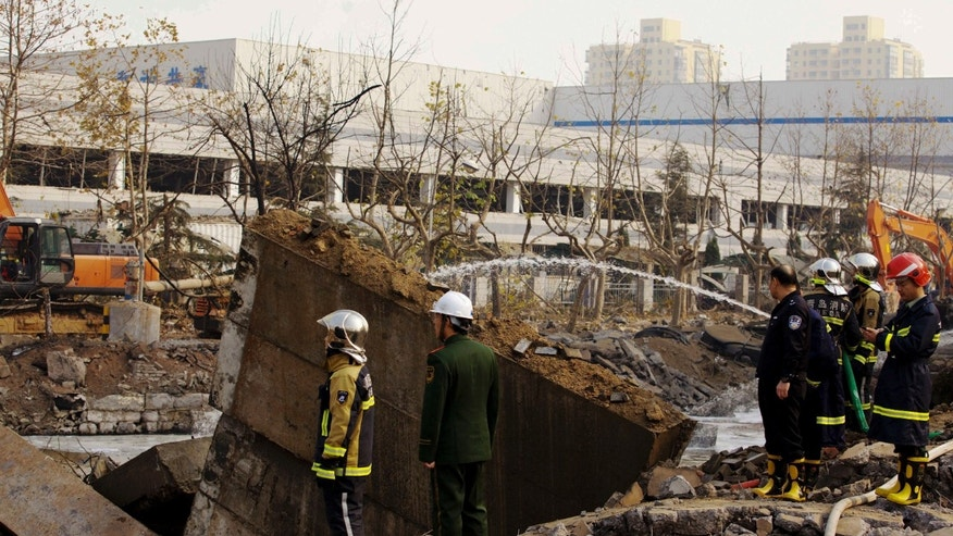 Policemen and firefighters work on a damaged site following a pipeline explosion in Qingdao in east China's Shandong province Friday, Nov. 22, 2013. Leaked oil from a ruptured oil pipe, owned by China's largest oil refiner, Sinopec, caught fire and exploded Friday in an eastern Chinese port city, killing and injuring many people. (AP Photo) CHINA OUT