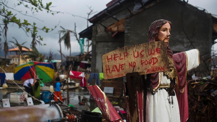 A plea for help painted on a sign hangs from a damaged statue of Jesus in a Typhoon Haiyan destroyed neighborhood in Tacloban, Philippines on Friday Nov. 22, 2013. Hundreds of thousands of people were displaced by Typhoon Haiyan, which tore across several islands in the eastern Philippines on Nov. 8. (AP Photo/David Guttenfelder)