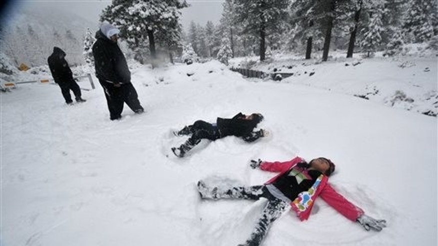 Darius Gomez, 9, center, and Amanda Lopez, 7, both from Palmdale, Calif, make snow angels together during their visit to Wrightwood, Calif, on Friday, Nov 22, 2013.  (AP Photo/The Victor Valley Daily Press, David Pardo)