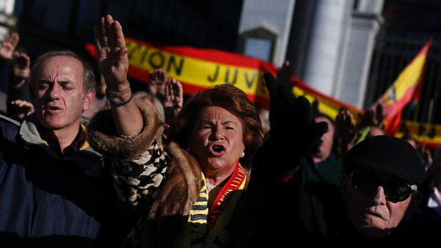 Fascists and far right wing supporters salute the fascist anthem as they remember former Spanish Dictator Gen. Francisco Franco on the 38th anniversary of his death, in Madrid, Spain, Sunday, Nov. 24, 2013. Hundreds of people nostalgic for Spain's fascist past held a rally on Sunday to mark the 38th anniversary of dictator Francisco Franco's death. The peaceful demonstration was held in Madrid's central Plaza de Oriente square near the opera and Royal Palace in the city's old quarter. On Saturday an anti-Franco protest was held northwest of Madrid at Franco's mausoleum. (AP Photo/Andres Kudacki)