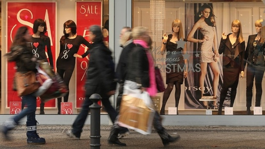 BERLIN, GERMANY - DECEMBER 17:  People walk by a clothing store adevertising sales on a shopping street in Steglitz district on December 17, 2012 in Berlin, Germany. Retailers are hoping for a strong Christmas season in Germany, one of the few countries whose economy has so far weathered the current Eurozone debt crisis relatively well.  (Photo by Sean Gallup/Getty Images)