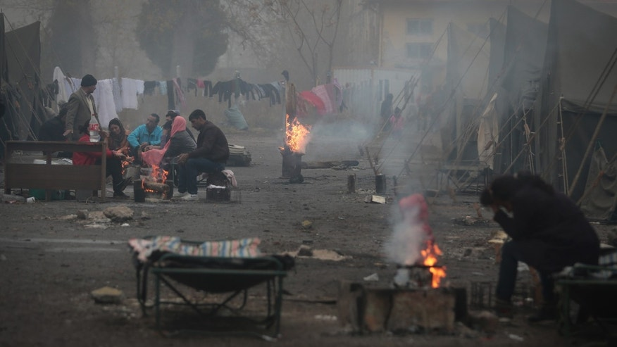 Syrian refugees try to stay warm near open fires in front of their unheated tents in a refugee camp in the town of Harmanli, Bulgaria, Thursday, Nov. 21, 2013.  Thousands of Syrian and other refugees from the Middle East, Asia and Africa, who find enough courage to make a dangerous journey from their war-ravaged states, often end up in the crammed settlements in the Balkans, including Bulgaria, Greece or Serbia, after being caught on the borders of wealthy Western European nations for attempting to cross illegally. (AP Photo/Valentina Petrova)