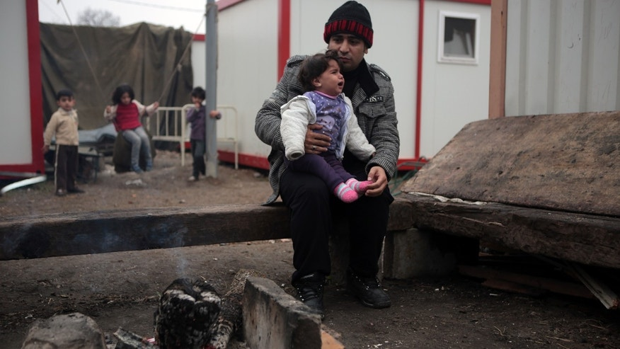 Hikmat Krad, 31 holding his one-year-old daughter, Kayana, sitting near their unheated caravan in a refugee camp in the town of Harmanli, Bulgaria, Thursday, Nov. 21, 2013. Thousands of Syrian and other refugees from the Middle East, Asia and Africa, who find enough courage to make a dangerous journey from their war-ravaged states, often end up in the crammed settlements in the Balkans, including Bulgaria, Greece or Serbia, after being caught on the borders of wealthy Western European nations for attempting to cross illegally. (AP Photo/Valentina Petrova)