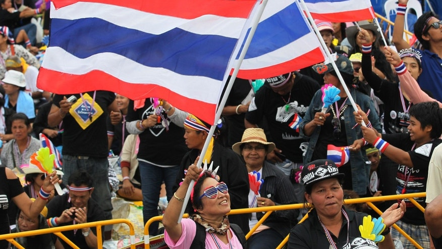 Anti-government protesters hold national flags and chant slogans in Bangkok, Thailand, Sunday, Nov. 24, 2013, calling for Thai Prime Minister Yingluck Shinawatra to step down.(AP Photo/Sakchai Lalit)