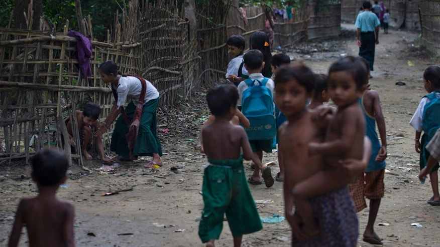 In this Sept. 13, 2013 photo, children of Lay Maing village walk on a street in Maungdaw, northern Rakhine state, Myanmar. Northern Rakhine state, which stretches along most of Myanmar's coast on the Bay of Bengal, is one of the poorest, most remote, isolated corners of this Southeast Asian nation. It's also home to 800,000 Rohingya, described by the U.N. as one of the most neglected ethnic minorities in the world. (AP Photo/Gemunu Amarasinghe)
