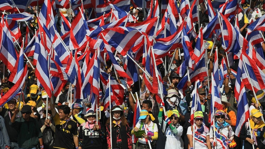 Anti-government protesters hold Thai national flags during a rally in Bangkok Monday, Nov. 25, 2013. Bangkok braced for major disruptions Monday as a massive anti-government march fanned out to 13 locations in a growing bid to topple the government of Prime Minister Yingluck Shinawatra. (AP Photo/Sakchai Lalit)