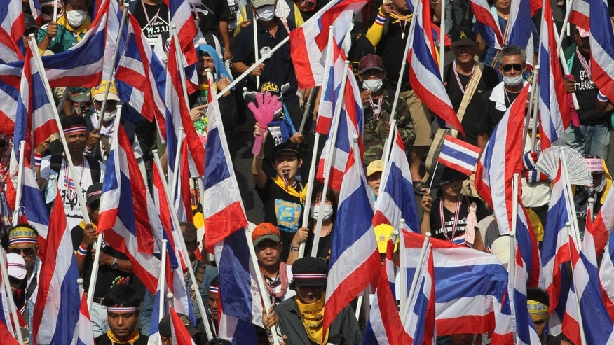 Anti-government protesters hold Thai flags during a rally in Bangkok Monday, Nov. 25, 2013. Bangkok braced for major disruptions Monday as a massive anti-government march fanned out to 13 locations in a growing bid to topple the government of Prime Minister Yingluck Shinawatra. (AP Photo/Sakchai Lalit)