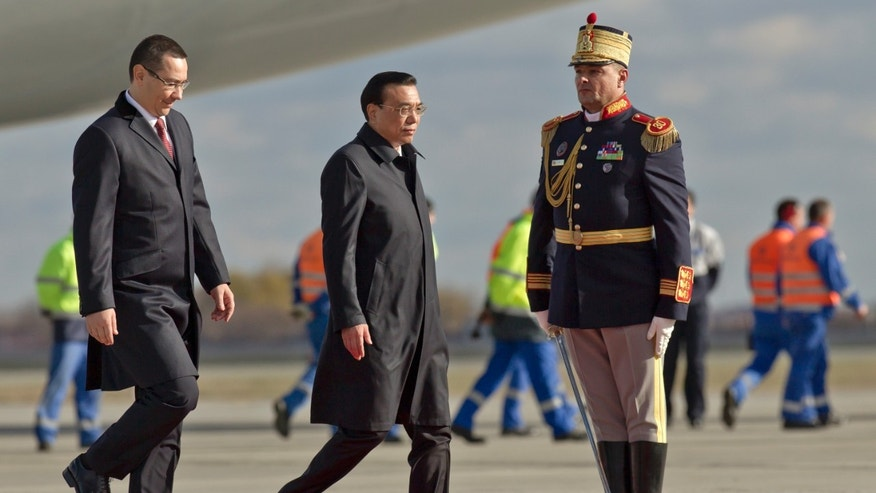 China's Premier Li Keqiang, right, walks next to the Prime Minister of Romania Victor Ponta, left, upon arriving at the Henri Coanda airport, outside Bucharest, Romania, Monday, Nov. 25, 2013. China's Premier will attend the China - Central and Eastern Europe meeting of heads of government, starting Tuesday in the Romanian capital.(AP Photo/Vadim Ghirda)